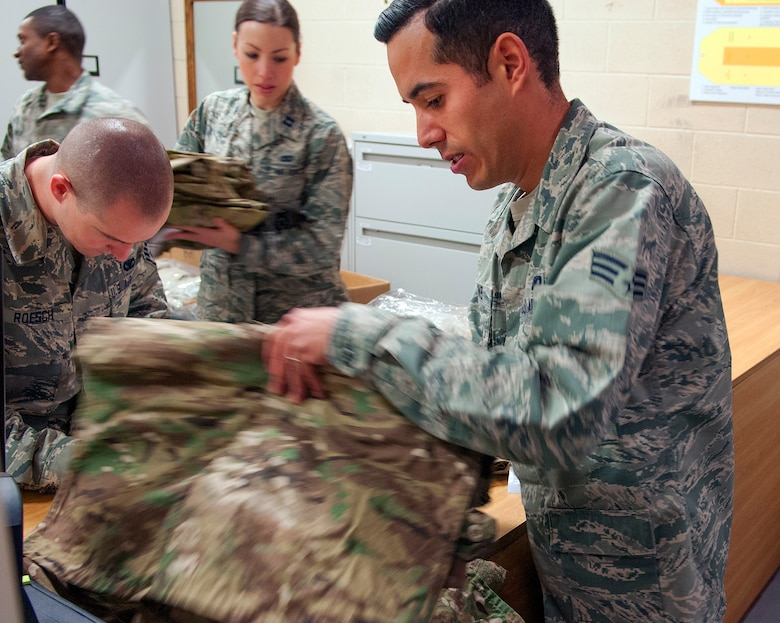 Senior Airman Tyler Collins, 790th Missile Security Forces Squadron Security Support Team, looks through his new Operation Enduring Freedom Camouflage Pattern uniforms Feb. 2, 2015, in the Peacekeeper High Bay on F.E. Warren Air Force Base, Wyo. Defenders who travel out to the missile field received new gear and uniforms as part of the 20th Air Force Model Defender Program. (U.S. Air Force photo by Airman 1st Class Brandon Valle)
