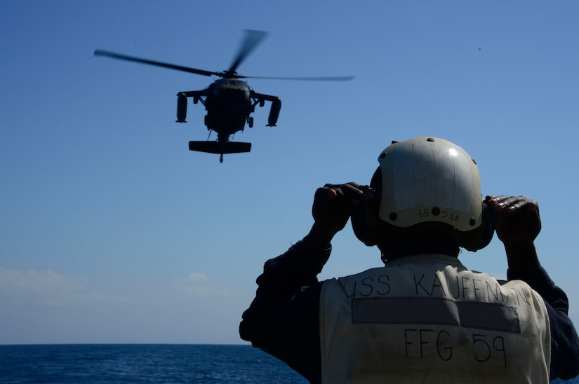 A U.S. Navy landing signal officer helps the members of the 1st Battalion, 228th Aviation Regiment land a UH-60 Blackhawk helicopter during deck landing qualifications off the coast of Honduras, Feb. 1, 2015.  The 1-228th Avn. Reg. aircrew participated in deck landing qualifications on board the USS Kauffman to qualify pilots and crew chiefs on shipboard operations.   Kauffman is on its final scheduled deployment to the U.S. Southern Command area of responsibility supporting multinational, counter-narcotics operation known as Operation Martillo. (U.S. Air Force photo/Tech. Sgt. Heather Redman)