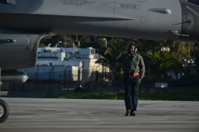 U.S. Air Force Airman 1st Class Kendrick Hargrove, a dedicated crew chief assigned to the 52nd Expeditionary Aircraft Maintenance Squadron, salutes as an F-16 Fighting Falcon fighter aircraft pilot assigned to the 480th Expeditionary Fighter Squadron taxis on the flightline during a flying training deployment at Souda Bay, Greece, Jan. 30, 2015. The aircraft conducted the training as part of the bilateral deployment between the Greek and U.S. Air Forces to develop interoperability and cohesion between the two NATO partners. (U.S. Air Force photo by Staff Sgt. Joe W. McFadden/Released)