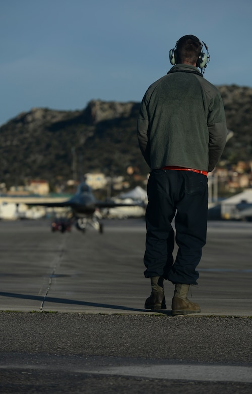U.S. Air Force Airman 1st Class Zachary Jung, an assistant crew chief assigned to the 52nd Expeditionary Aircraft Maintenance Squadron, observes as an F-16 Fighting Falcon fighter aircraft pilot assigned to the 480th Expeditionary Fighter Squadron taxis on the flightline during a flying training deployment at Souda Bay, Greece, Jan. 30, 2015. Jung used a series of hand gestures and movements to convey to the pilot whether to stop or keep moving while the aircraft taxied on the flightline. (U.S. Air Force photo by Staff Sgt. Joe W. McFadden/Released)