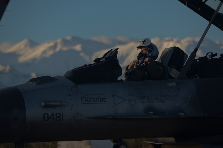 A U.S. Air Force F-16 Fighting Falcon fighter aircraft pilot assigned to the 480th Expeditionary Fighter Squadron fastens his breathing mask onto his helmet while in the aircraft's cockpit on the flightline during a flying training deployment at Souda Bay, Greece, Jan. 30, 2015. The aircraft conducted the training as part of the bilateral deployment between the Greek and U.S. Air Forces to develop interoperability and cohesion between the two NATO partners. (U.S. Air Force photo by Staff Sgt. Joe W. McFadden/Released)