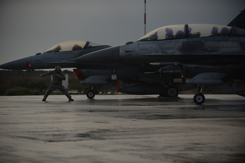 U.S. Air Force Airman 1st Class Zachary Jung, an assistant crew chief assigned to the 52nd Expeditionary Aircraft Maintenance Squadron, signals an F-16 Fighting Falcon fighter aircraft assigned to the 480th Expeditionary Fighter Squadron for departure from the flightline during a flying training deployment at Souda Bay, Greece, Jan. 29. 2015. Jung, along with 300 personnel from Spangdahlem Air Base, Germany, participated in the flying training deployment between the Hellenic and U.S. Air Forces at Souda Bay, Jan. 16-Feb. 13, 2015. (U.S. Air Force photo by Staff Sgt. Joe W. McFadden/Released)