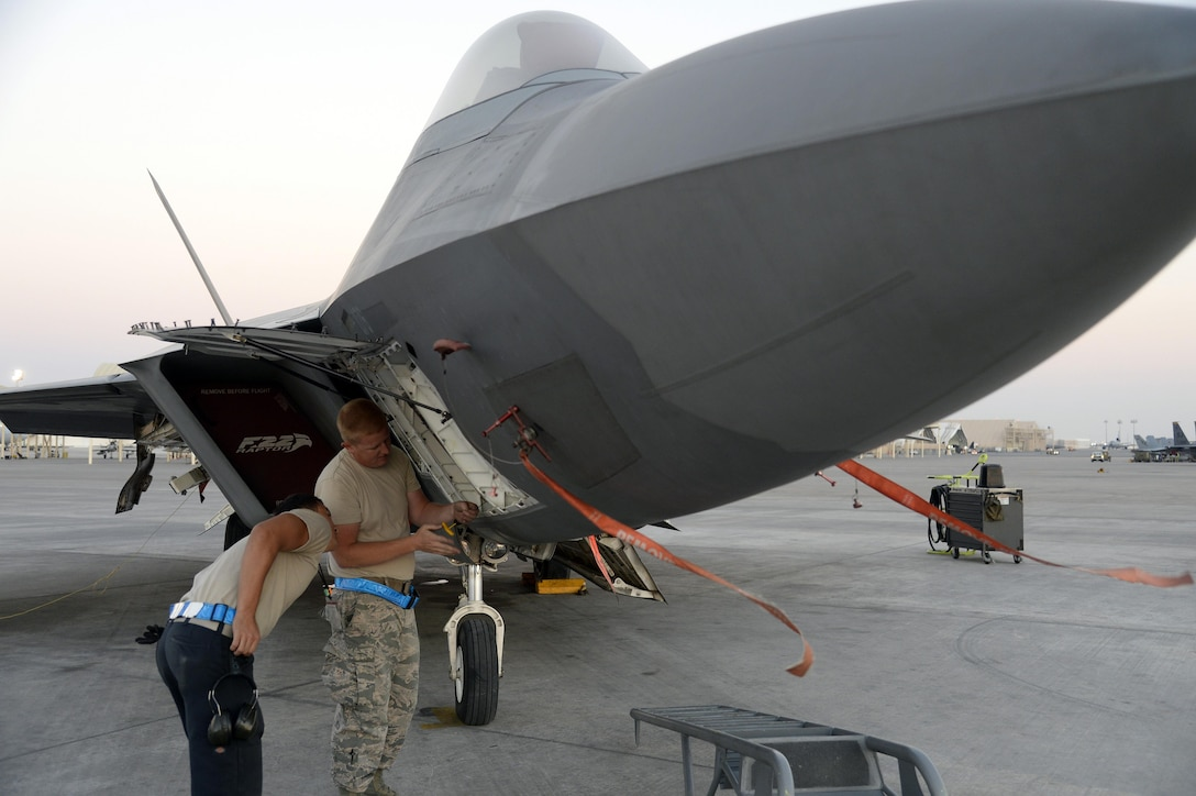 Staff Sgt. James, avionics craftsman, right, and Senior Airman Dakota, launch assist, troubleshoots a communications, navigation and identification system on an F-22 Raptor at an undisclosed location in Southwest Asia Jan. 26, 2015. The F-22 Raptor is the first aircraft to use integrated avionics, where the radar, weapons management system and electronic warfare system work as one, giving the pilot unprecedented situational awareness. James is currently deployed from Tyndall Air Force Base, Fla., and is a native of Frackville, Pa. Dakota is currently deployed from Tyndall AFB, Fla., and is a native of El Paso, Texas. (U.S. Air Force/Tech. Sgt. Marie Brown)