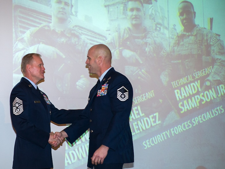 Chief Master Sgt. of the Air Force James Cody congratulates Master Sgt. Michael Sears after Cody gave the keynote address during a luncheon honoring Sears and the other Airmen from the Air Force's ninth volume of Portraits in Courage, Feb. 4, 2015, in, Arlington, Va. During the luncheon the Airmen told their stories to a group of Air Force civic leaders from around the country. Portraits in Courage is an Air Force program highlighting Airmen for their honor, valor, devotion and selfless sacrifice in the face of extreme danger to themselves and others. (U.S. Air Force photo/Jim Varhegyi)
