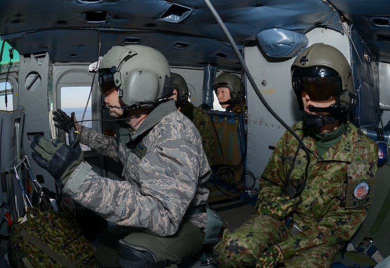 Members of the Japan Ground Self-Defense Force (JGSDF) ride along with U.S. service members as they perform formation maneuvers during a bilateral training mission Jan. 29, 2015, near Tokyo. U.S. and JGSDF members conducted the exchange mission to deepen their understanding of each other's tactics, techniques and procedures. (U.S. Air Force photo/Senior Airman Michael Washburn)