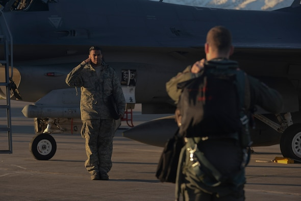 U.S. Air Force Staff Sgt. Christopher Pridgen salutes an F-16 Fighting Falcon pilot Jan. 30, 2015, during a flying training deployment at Souda Bay, Greece. Crew chiefs perform pre-flight and secondary inspections of the aircraft before pilots taxi the aircraft to the flightline for takeoff. Pridgen is a crew chief assigned to the 52nd Expeditionary Aircraft Maintenance Squadron and the pilot is assigned to the 480th Expeditionary Fighter Squadron. (U.S. Air Force photo/Staff Sgt. Joe W. McFadden)