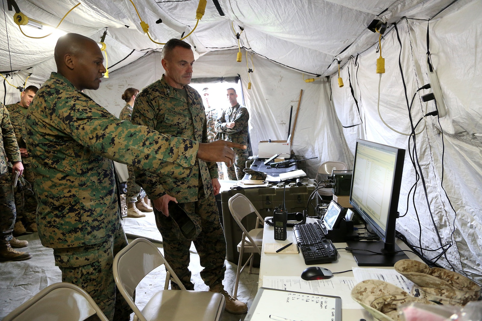 Major Elishama Wheeler, G-6 Operations Officer, Headquarters Regiment, 1st Marine Logistics Group, explains an emerging communications capability called digital interoperability to Maj. Gen. Vincent A. Coglianese, 1st MLG Commanding General, during an en-route care exercise aboard Camp Pendleton, Calif., Jan. 28, 2015. During the four-day exercise, corpsmen trained to prepare a Special-Purpose Marine Air-Ground Task Force group that is going to forward deploy later this year. The more than 40 corpsmen set up a shock trauma platoon facility, or mobile emergency room, to treat simulated casualties. The casualties were stabilized in the STP and then flown out via aircraft. (U.S. Marine Corps photo by Sgt. Laura Gauna/Released)