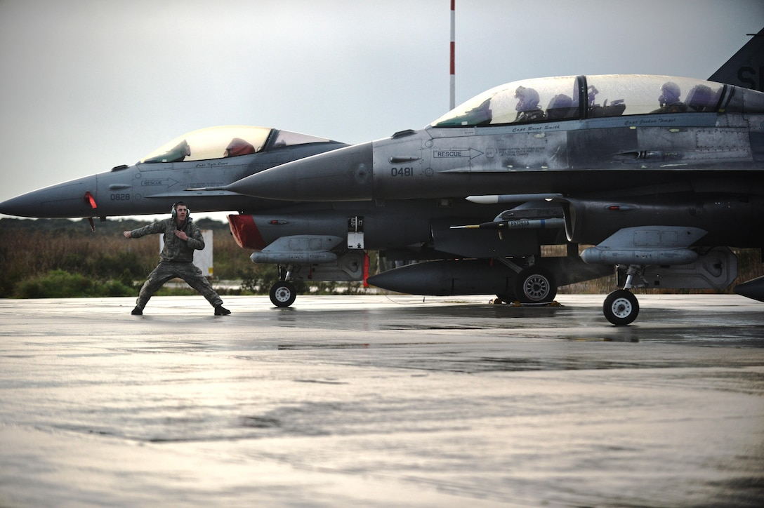 Airman 1st Class Zachary Jung signals an F-16 Fighting Falcon for departure Jan. 29, 2015, during a flying training deployment at Souda Bay, Greece. Jung, along with 300 personnel from Spangdahlem Air Base, Germany, are participating in the flying training deployment between the Hellenic and U.S. air forces at Souda Bay, from Jan. 16-Feb. 1. Jung is an assistant crew chief assigned to the 52nd Expeditionary Aircraft Maintenance Squadron, and the F-16 is assigned to the 480th Expeditionary Fighter Squadron. (U.S. Air Force photo/Staff Sgt. Joe W. McFadden)