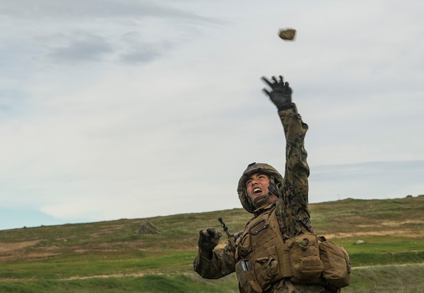 U.S. Marine Pfc. Joseph Aspiras throws a simulated grenade during squad tactics and maneuver training aboard Camp Pendleton, Calif., Jan. 26, 2015. Aspiras is a rifleman with Kilo Company, Battalion Landing Team 3rd Battalion, 1st Marine Regiment, 15th Marine Expeditionary Unit. As the ground combat element for the 15th MEU, BLT 3/1 is preparing for their upcoming deployment by enhancing their combat skills and learning to work as a cohesive unit. (U.S. Marine Corps Photo by Sgt. Emmanuel Ramos/Released)