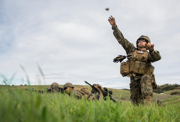 U.S. Marine Pfc. Cody Dunlap throws a simulated grenade during squad tactics and maneuver training aboard Camp Pendleton, Calif., Jan. 26, 2015. Dunlap is an automatic rifleman with Kilo Company, Battalion Landing Team 3rd Battalion, 1st Marine Regiment, 15th Marine Expeditionary Unit. As the ground combat element for the 15th MEU, BLT 3/1 is preparing for their upcoming deployment by enhancing their combat skills and learning to work as a cohesive unit. (U.S. Marine Corps Photo by Sgt. Emmanuel Ramos/Released)