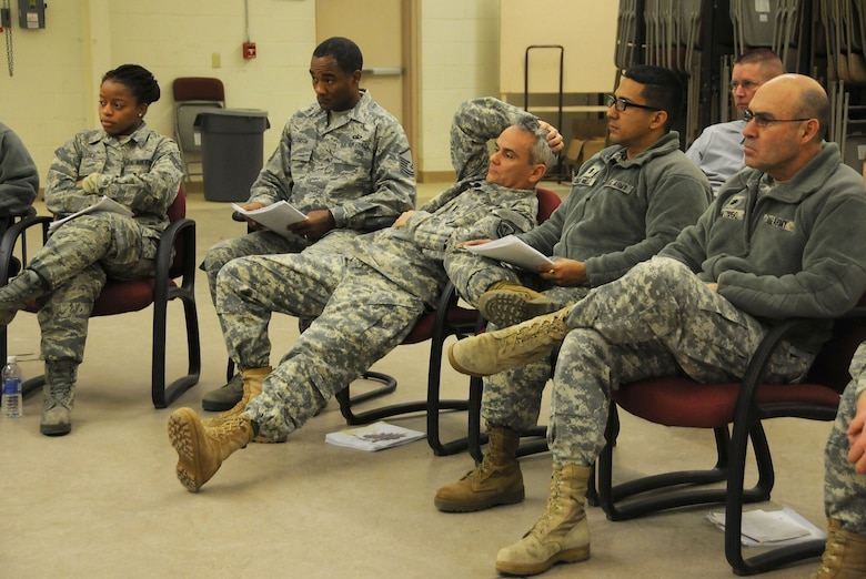 Army and Air Force chaplains and chaplain assistants from all over N.J., sit at a simulated discussion during the Traumatic Event Management Course Jan. 16, 2015, at Joint Base McGuire-Dix-Lakehurst, N.J. The scenario discussion took place after a fictitious plane crash and the members each had different roles to portray. In the center, Army Capt. Shawn Found, a chaplain from the 117th Combat Sustainment Support battalion, plays a character who doesn't want to participate and acts rude during the discussion. The Army's TEM course is a week long and focuses on unit cohesion and effectiveness to help manage crisis situations. The course focuses on group activities and role playing to reinforce the lessons. At the end of the week, the students are able to take what they learned and bring it back to their units. (U.S. Air National Guard Photo by Airman 1st Class Julia Pyun/Released)