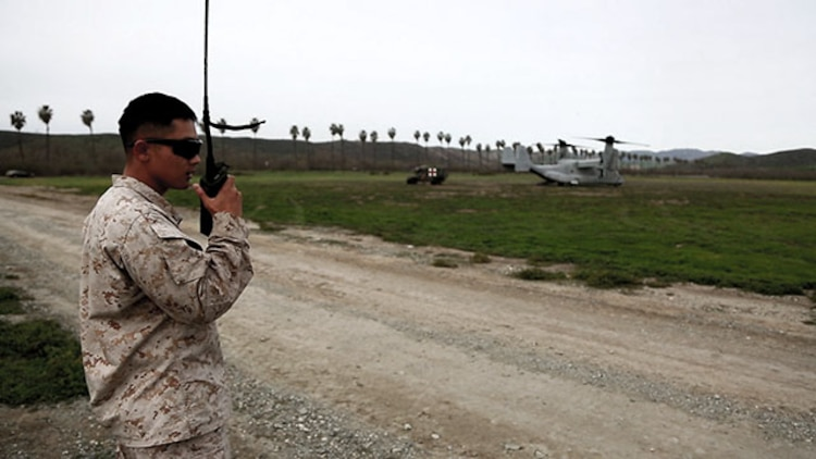 A data network specialist from Headquarters Regiment, 1st Marine Logistics Group, communicates with an MV-22 Osprey pilot during an en-route care exercise aboard Camp Pendleton, Calif., Jan. 28, 2015. During the four-day exercise, corpsmen trained to prepare a Special-Purpose Marine Air-Ground Task Force group that is going to forward deploy later this year. The more than 40 corpsmen set up a shock trauma platoon facility, or mobile emergency room, to treat simulated casualties. The casualties were stabilized in the STP and then flown out via aircraft. (U.S. Marine Corps photo by Sgt. Laura Gauna/Released)