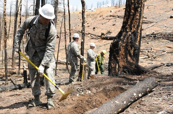 Cadet 1st Class Broam Hart helps move logs in order to prevent flooding after the Waldo Canyon fire in June, 2013. Hart participates in a variety of volunteer work, in addition to playing for the Academy football team and his academics. (Courtesy photo)