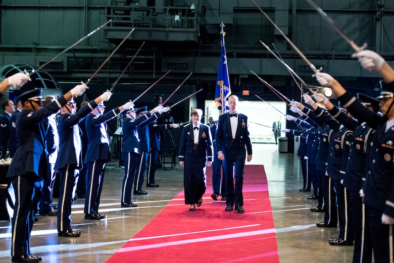 Gen. Janet Wolfenbarger, Air Force Materiel Command commander, is joined by AFMC Command Chief Master Sgt. Michael Warner as she enters her Order of the Sword induction ceremony through a formation of sabers raised by an Honor Guard. The ceremony, held Feb. 5, 2015, at the National Museum of the United States Air Force, was steeped in medieval symbolism and military tradition, and paid tribute to the general's servant leadership. The Order of the Sword is the highest honor Air Force noncommissioned officers can bestow upon an individual who has made significant contributions to the enlisted force. (U.S. Air Force photo by Wesley Farnsworth)