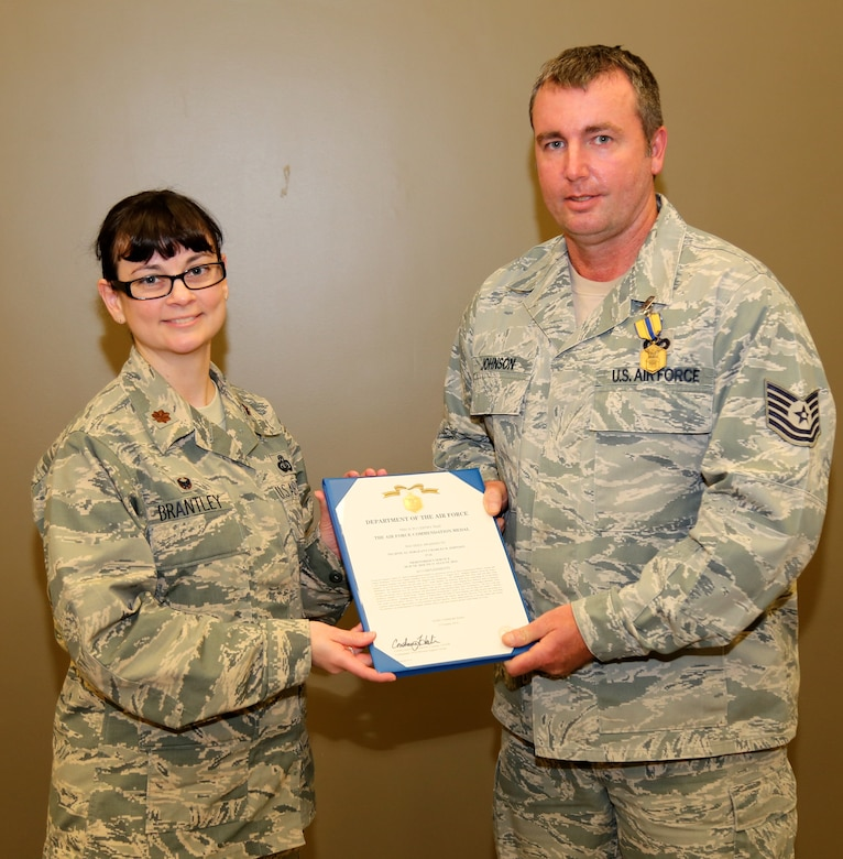 Maj. Amy Brantley presents the Air Force Commendation Medal for Meritorious Service to Technical Sergeant Charles Johnson for his outstanding work in the family readiness office at the 932nd Force Support Squadron, 932nd Airlift Wing.  (U.S. Air Force photo/Maj. Stan Paregien)