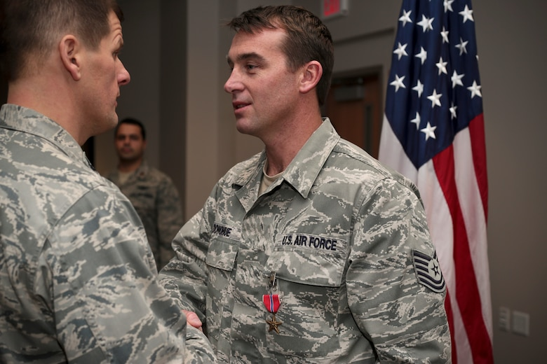 New Jersey Air National Guard Tech. Sgt. Christopher Donohue, right, is congratulated by Col. Kerry M. Gentry, commander of the 177th Fighter Wing, after receiving the Bronze Star Medal at Atlantic City Air National Guard Base, N.J., Feb. 8, 2015. Donohue, a Joint Terminal Attack Controller with the 227th Air Support Operations Squadron was recognized for his efforts in support of Operation Enduring Freedom. He was deployed to Afghanistan with soldiers from the New Jersey Army National Guard and the Albanian military as an advisor for the Afghan National Army's (ANA) 1st Mobile Strike Force (MSF). Donohue participated in over one hundred combat missions in which he directly engaged enemy forces. (U.S. Air National Guard photo by Tech. Sgt. Matt Hecht)