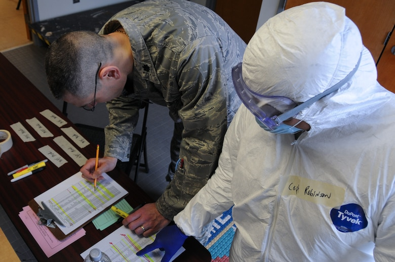 U.S. Air Force Lt. Col. Eric Erickson and Capt. Lisa Robinson with the New Jersey Air National Guard's 177th Fighter Wing Medical Group in Egg Harbor Township, N.J., looks over information on the number of simulated exposures and infections during the base's Disease Containment Exercise on Feb. 8, 2015. The base simulated responding to an Ebola outbreak making sure the base stays mission ready at all times. (U.S. Air National Guard photo by Airman 1st Class Amber Powell)