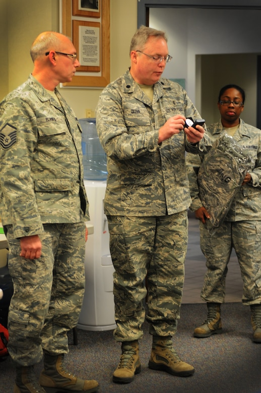Lt. Col. John Dunn, 111th Attack Wing medical group commander, presents Master Sgt. Christopher Eliades, 111th ATKW medical group, with a coin in recognition of his six-year reenlistment commitment while Staff Sgt. Jovan Tate, 111th ATKW Education and Training Office, stands by to give Eliades a gift that is presented to those who reenlist for the full six years, Feb. 8, 2015, Horsham Air Guard Station, Pa. The new reenlistment recognition program was initiated by the National Guard Bureau with recruiting squadrons and education and training offices, a combined force known as the strength retention team, implementing the program.(U.S. Air National Guard photo by Tech. Sgt. Andria J. Allmond/Release)