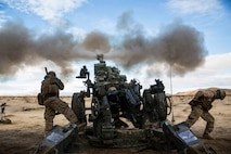 """Lance Cpl. Christian J. Hernandez (left) and Lance Cpl. Giovonni Mejia fire the M777A2 lightweight 155 mm howitzer Jan. 31 to support units engaged in the mechanized assault course at Marine Air Ground Combat Center Twentynine Palms during Integrated Training Exercise 2-15. """"Fighting with combined arms is on of the most important parts of the (Marine Air-Ground Task Force),"""" said Lt. Col. Neil J. Owens. Giovonni, a Dallas, Texas native and Hernandez, a Buford, Georgia, native are both cannoneers with 1st Battalion, 12th Marine Regiment, currently assigned to 3rd Battalion, 12th Marines, 3rd Marine Division, III Marine Expeditionary Force for ITX 2-15, as part of the ground combat element for SPMAGTF-4. Owens, a Medford, Massechusetts, native, is the commanding officer for 3rd Bn., 12th Marines."""