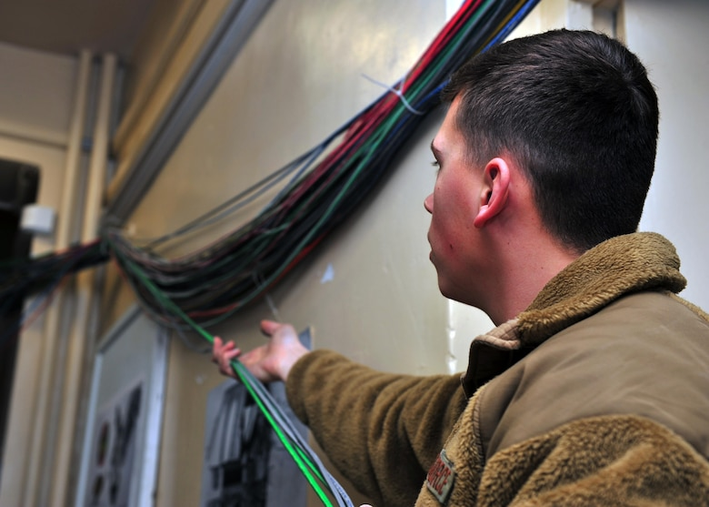 U.S. Air Force Senior Airman James Jarvis, 85th Engineering and Installation Squadron cable and antenna technician, gathers cables prior to feeding them through network cable paths as part of a rewiring project Jan. 28, 2015 at Bagram Airfield, Afghanistan. The project, scheduled to take 100 days to complete, will ensure Emissions Security requirements are upheld and prevent secure information from being leaked through emanation. (U.S. Air Force photo by Staff Sgt. Whitney Amstutz/released)