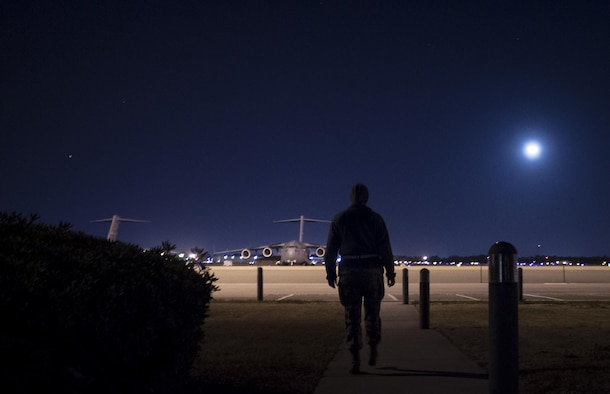 Senior Airman Kathryn Raethel  walks from the base operations building out to the flightline to look for any damaged or burnt out runway lights, as well as directional signs used by aircraft Feb. 9, 2015, at Joint Base Charleston, S.C. Whenever an in-flight emergency occurs, base operations is notified and begins informing several different agencies to handle the delicate situation. Raethel is a 437th Operations Support Squadron airfield management technician. (U.S. Air Force photo/Senior Airman Dennis Sloan)