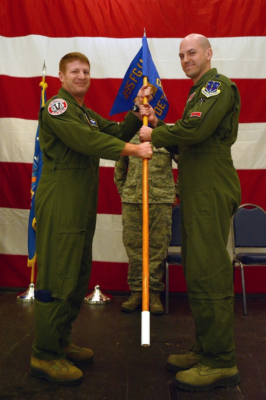 Lt. Col. J. Scott Gibson, commander of the 495th Fighter Group's Detachment 176, receives command from Col. James D. McCune, 495th Fighter Group commander, during an assumption of command ceremony in Hangar 406 on Truax Field, Madison, Wis., Feb. 7, 2015. Gibson will ultimately be responsible for 40 active duty personnel and four pilots at the 115th Fighter Wing as part of the Air Force's total force integration, a program designed to integrate active duty and guard Airmen. (U.S. Air National Guard photo by Senior Airman Andrea F. Rhode)