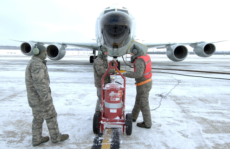 U.S. Air Force Staff Sgt. Vincent Vasquez, left, U.S. Air Force Airman 1st Class Jordan Scott and Senior Airman Jacob Bryson, right, standby while preparing an RC-135 Rivet Joint for launch Feb. 3 at Offutt Air Force Base Neb. Additional maintenance time is typically needed during winter operations to heat aircraft and to remove snow and ice from the aircraft prior to take-off.  They are all crew chiefs assigned to the 83rd Aircraft Maintenance Unit, 55 Aircraft Maintenance Squadron. (U.S. Air Force photo by Delanie Stafford/Released)