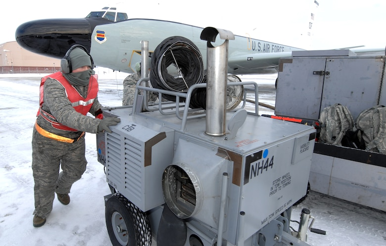 U.S. Air Force Senior Airman Jacob Bryson and another airman push a heater cart out of the path of an RC-135 Rivet Joint while preparing the aircraft for launch Feb. 3 at Offutt Air Force Base Neb. Additional maintenance time is typically needed during winter operations to heat aircraft and to remove snow and ice from the aircraft prior to take-off.   Bryson is a crew chief assigned to the 83rd Aircraft Maintenance Unit, 55 Aircraft Maintenance Squadron. (U.S. Air Force photo by Delanie Stafford/Released)