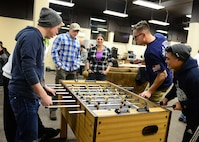 Airmen play a game on the foos ball table at the Icebox in building 2266 during an Airman's Dinner at Eielson Air Force Base, Alaska, Jan. 20, 2015. (U.S. Air Force photo by Senior Airman Ashley Nicole Taylor/Released)