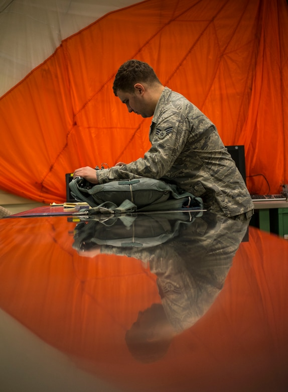 Senior Airman Justin Turner, 437th Operations Support Squadron Aircrew Flight Equipment technician, inspects a parachute before storing it for future use Feb. 9, 2015, at Joint Base Charleston, S.C. AFE works through the night to provide aircrew members with safe and reliable equipment, including night vision goggles, helmets, masks and even parachutes. (U.S. Air Force photo/ Senior Airman Dennis Sloan)
