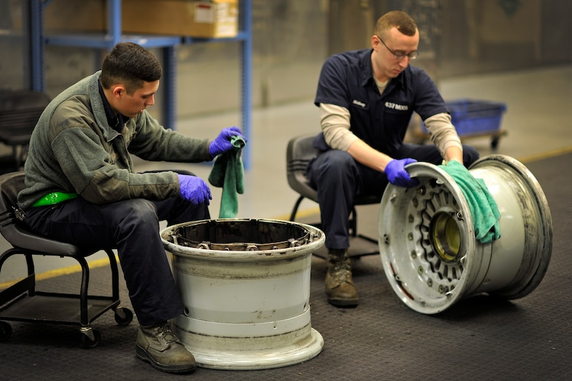 Senior Airman Terron Charles (left) and Senior Airman Bradley Matheny, crew chiefs with the 437th Maintenance Squadron, work in the aircraft recovery section cleaning tire rims at Joint Base Charleston, S.C., Feb. 9, 2015. While in the repair and reclamation section, these crew chiefs are expected to perform crash recovery, aero repairs, and wheel and tire maintenance. Their job continues both day and night. (U.S. Air Force photo/Tech. Sgt. Renae Pittman)