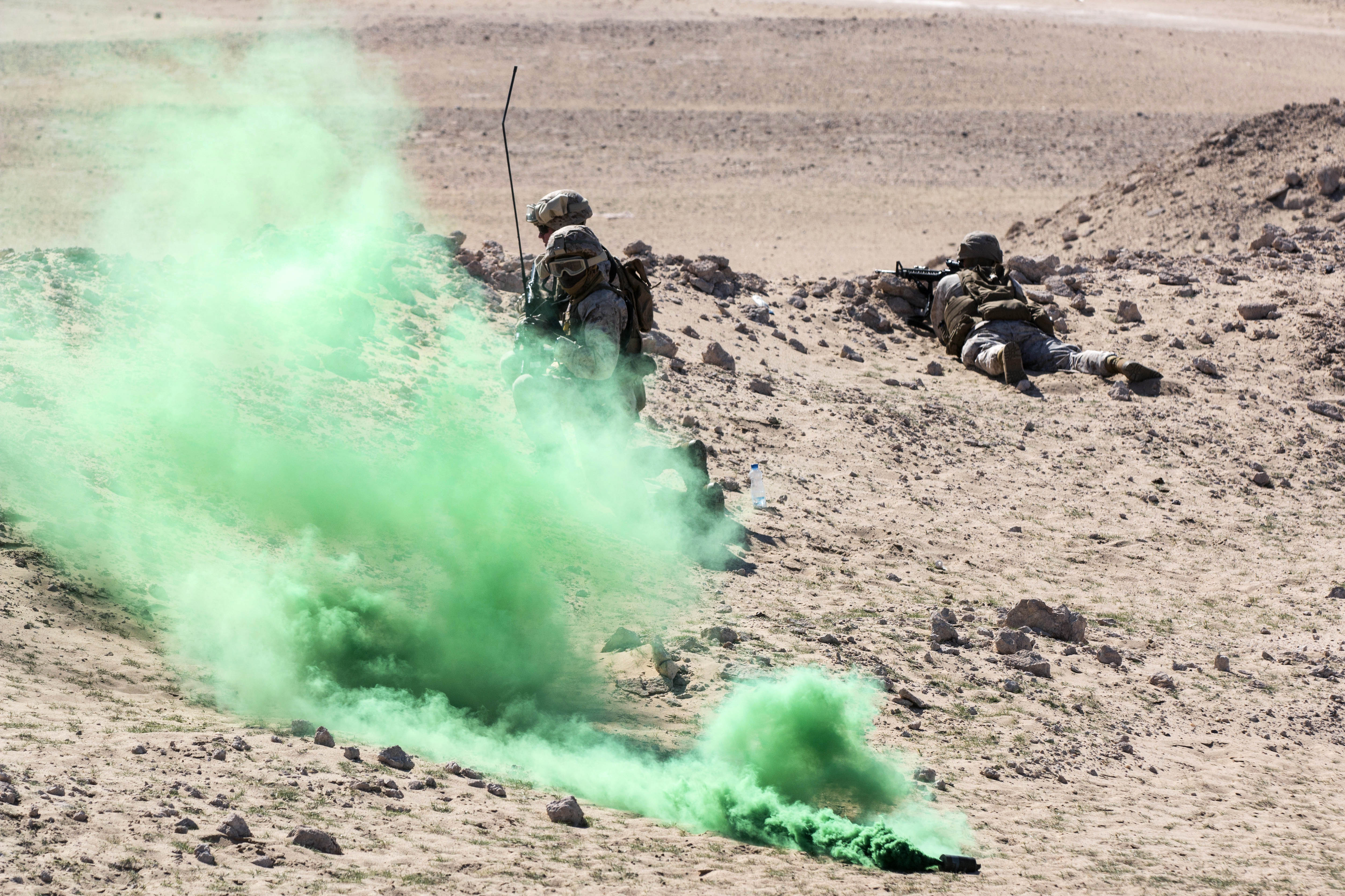 A green smoke grenade is used to signal a UH-60 Black Hawk