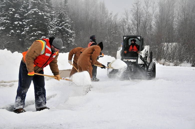Members of the Alaska Department of Environmental Conservation, 611th Civil Engineer Squadron, and U.S. Navy Supervisor of Salvage and Diving set up the rope mop skimmer during an Arctic oil spill response exercise Feb. 4, 2015, in Alaska. A trench is dug a certain depth in the ice and holes are drilled to allow the oil/product to rise up into the trench to be collected. The skimmer rotates through the trench collecting the oil and sends it to a holding tank. The units participated in the exercise to learn Arctic spill response tactics and techniques. (U.S. Air Force photo/Tech. Sgt. John Gordinier)