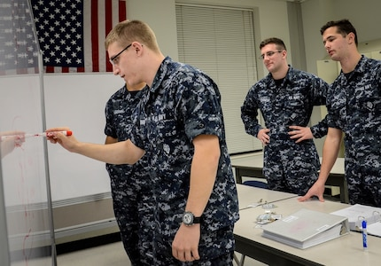Naval Nuclear Power Training Command students study well into the night using a dry erase board to solve equations and prepare for their next exam Feb. 9, 2015, at Joint Base Charleston Weapons Station. NNPTC classrooms remain open until midnight, so students can study any part of the curriculum. Instructors also stay after hours to work with Sailors individually, which is not always possible during a typical school day.  (U.S. Air Force photo/ Senior Airman Dennis Sloan)