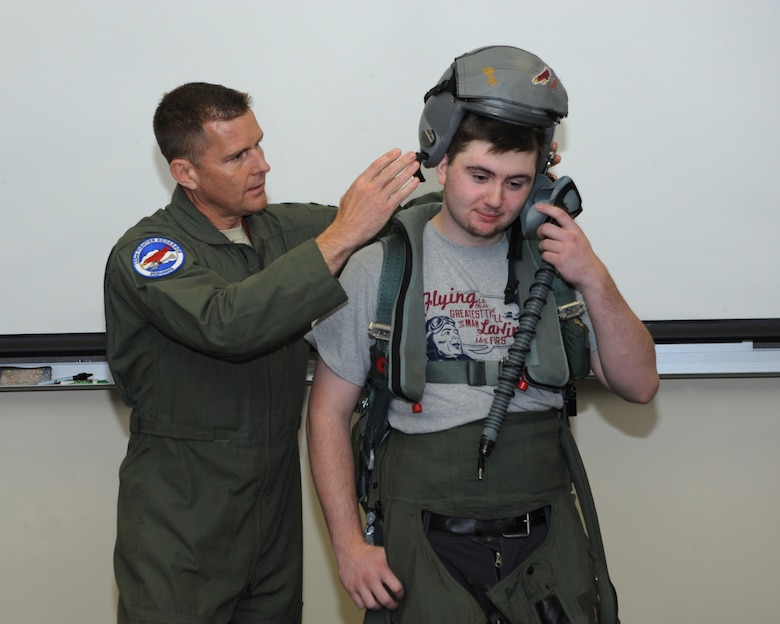 Col. Richard Wedan, 142nd Fighter Wing commander helps fit a pilot helmet to students touring the Portland Air National Guard Base, Ore., Oct. 16, 2014. (U.S. Air National Guard photo by Tech. Sgt. John Hughel/Released)