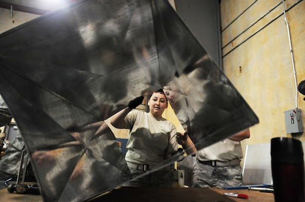 U.S. Air National Guard Airman 1st Class Jessica Ochoa from the 146th Airlift Wing Civil Engineering Squadron moves an air duct at the 554th Red Horse Squadron at Andersen AFB, Guam on February 4, 2015. (U.S. Air National Guard photo by Airman 1st Class Madeleine Richards/Released)
