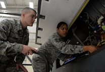 Tech. Sgt. Maureen Madamba (right), 372nd Training Squadron Detachment 21 maintenance instructor, instructs Airman Basic Lain Baker, 372nd TRS Detachment 21 student, how to properly inspect interior components of a RQ-4 Global Hawk Jan. 20, 2015, at Beale Air Force Base, Calif. Madamba is tasked with teaching the first class of the RQ-4 remotely piloted aircraft maintenance course. (U.S. Air Force photo by Senior Airman Bobby Cummings/Released)