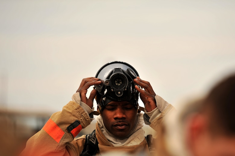 GOODFELLOW AIR FORCE BASE, Texas – Airman 1st Class Onnie O. McSpadden, 127th Michigan Air National Guard firefighting apprentice, readies his gas mask in preparation for firefighting training, Feb. 3. The air becomes thick with smoke and heat around the simulated burners, requiring the students to use oxygen tanks to breathe.