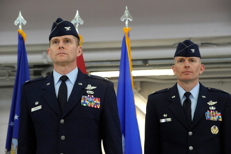 U.S. Air Force Col. Richard W. Wedan, outgoing commander 142nd Fighter Wing, left, and Col. Paul T. Fitzgerald, incoming commander 142nd Fighter Wing, right, stand at attention as orders for the citation for The Air Force Legion of Merit Medal are read and presented to Wedan during the Change of Command ceremony held Feb. 7, 2015, Portland Air National Guard Base, Ore. (U.S. Air National Guard photo by Tech. Sgt. John Hughel, 142nd Fighter Wing Public Affairs)
