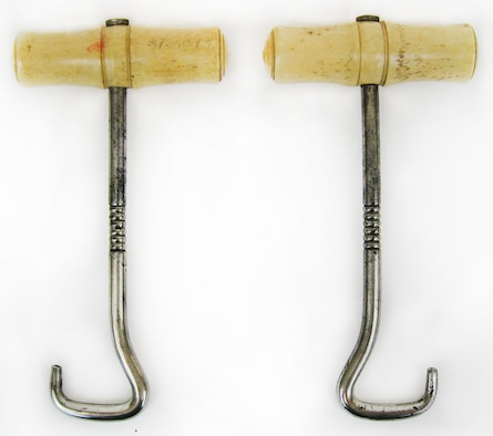 Boot hooks are designed to make pulling on tall riding boots a quick and easy process. Holding the handle of the boot hook, the hook ends of the boot hooks are then slipped through the boot pull straps attached on the sides of riding boots. Sometimes the boot straps are part of the external design of the boot, but usually these straps are hidden inside the boots (located at both sides near the top). (U.S. Air Force photo)