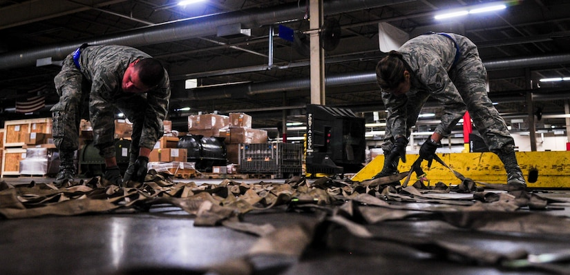 """Senior Airman Darwin Polo and Senior Airman Maria Harrison, 88th Aerial Port Squadron air transportation specialists, prepare straps used to secure a pallet Feb. 9, 2015, at the 437th Aerial Port Squadron on Joint Base Charleston, S.C. The """"Port Dawgs"""" work through the night to ensure the safe handling of cargo, for transportation throughout the world.(U.S. Air Force photo/Airman 1st Class Clayton Cupit)"""