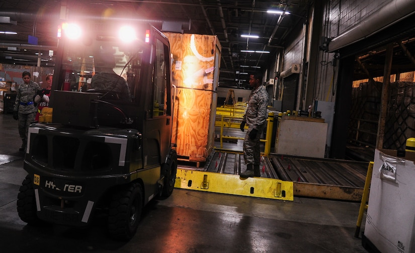 """Airmen from the 437th Aerial Port Squadron build a pallet Feb. 9, 2015, at the 437th APS on Joint Base Charleston, S.C. The need for safe, precise, reliable airlift never stops, and therefore neither do the """"Port Dawgs."""" They work through the night to process cargo and load it on and off Charleston's fleet of C-17 Globemaster IIIs. (U.S. Air Force/Airman 1st Class Clayton Cupit)"""