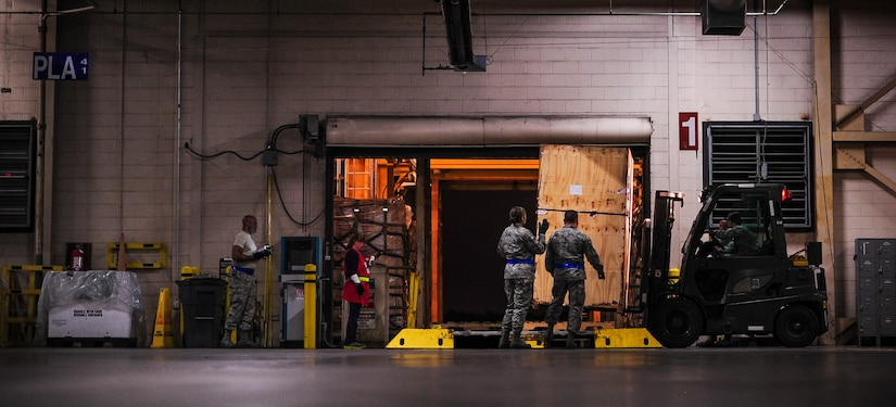 """Airmen from the 437th Aerial Port Squadron build a pallet Feb. 9, 2015, at the 437th APS on Joint Base Charleston, S.C. The """"Port Dawgs"""" work through the night to process cargo and load it on and off Charleston's fleet of C-17 Globemaster IIIs. (U.S. Air Force/Airman 1st Class Clayton Cupit)"""