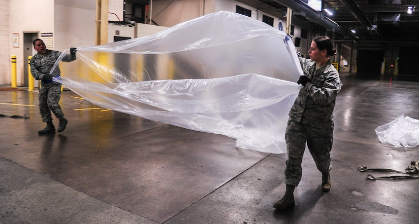 """Senior Airman Melissa Howerton and Senior Airmen Darwin Polo, 437th Aerial Port Squadron air transportation specialists, prepare to cover a pallet with a protective sheet Feb. 9, 2015, at Joint Base Charleston, S.C. The need for safe, precise, reliable airlift never stops, and therefore neither do the """"Port Dawgs."""" They work through the night to process cargo and load it on and off Charleston's fleet of C-17 Globemaster IIIs.(U.S. Air Force/Airman 1st Class Clayton Cupit)"""