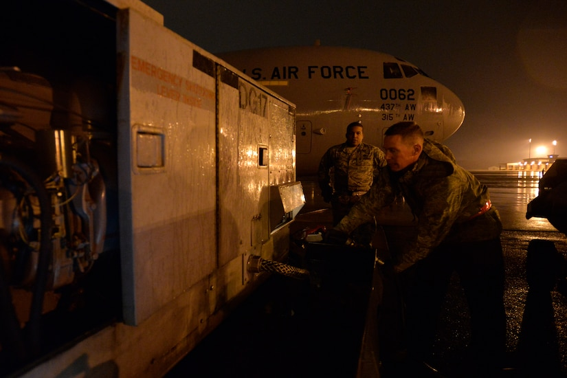 Staff Sgt. Gregory House, a quality assurance inspector with the 437th Maintenance Group, looks on as Staff Sgt. Timothy Womble, an aerospace ground equipment technician with the 437th Maintenance Squadron, refuels a generator during a rainy night at Joint Base Charleston, S.C., Feb. 9, 2015. Many units assigned to the 437th Airlift Wing work around the clock, no matter the weather, to ensure the mission gets done. (U.S. Air Force photo/Tech. Sgt. Renae Pittman)