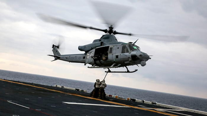 Landing support specialists attach a load of tires to a UH-1Y Huey attached to Marine Medium Tiltrotor Squadron 262, 31st Marine Expeditionary Unit, during a helicopter support team exercise Feb. 6 on the flight deck of the USS Bonhomme Richard. The Marines used a MK-105 cable, also known as the Q-tip, to hook the load onto the bottom of the Huey. The Marines are with Combat Logistics Battalion 31, 31st MEU, and are currently deployed in support of the annually-scheduled Spring Patrol of the Asia-Pacific region.