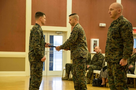 Newly appointed Sgt. Maj. Bradley Simmons (left), Sgt. Maj. of 8th Communication Battalion, 2nd Marine Headquarters Group, receives the Non-Commissioned Officer Sword from Lt. Col. Derek Lane, (center), the unit's commanding officer. The passing of the NCO Sword signifies the passing of responsibilities from the outgoing sergeant major to the incoming. (U.S. Marine Corps photo by Pfc. Dalton Precht/Released)