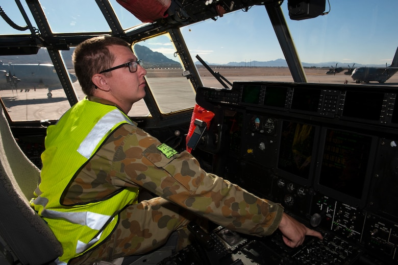 A Royal Australian air force aircraft maintainer prepares a C-130J Super Hercules from 37 Squadron, Richmond, Australia, for a training exercise during Red Flag 15-1 at Nellis Air Force Base, Nev., Feb. 7, 2015. In addition to increasing aircrew combat skills, Red Flag also increases ground crew combat readiness and effectiveness. (U.S. Air Force photo by Senior Airman Thomas Spangler)