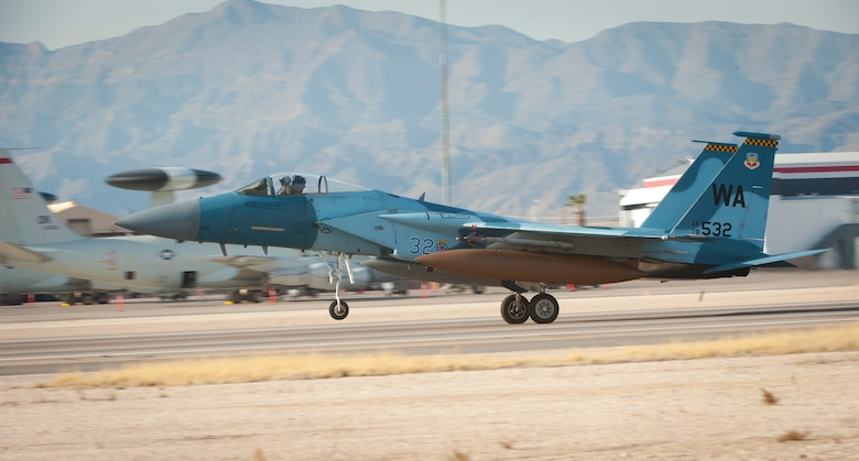 """An F-15C Eagle assigned to the 64th Aggressor Squadron, lands following the completion of a Red Flag 15-1 training sortie at Nellis Air Force Base, Nev., Feb. 4, 2015. Pilots and aircrews of the 64 AGRS, paired with space, cyber and intelligence experts within the 57th Adversary Tactics Group, present a credible threat picture for Red Flag coalition """"Blue Force"""" participants. . (U.S. Air Force photo by Airman 1st Class Joshua Kleinholz)"""