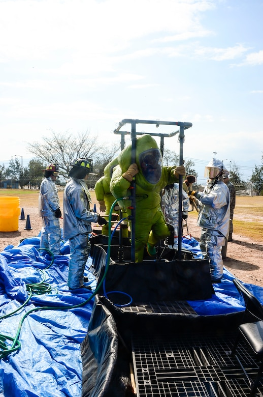 U.S. Air Force Airman 1st Classes Gregory Pease and Nolan Bailey, 612th Air Base Squadron firefighters, walk through a decontamination line during a hazardous material exercise on Soto Cano Air Base, Honduras, Feb. 10, 2015. The training exercise was held to guarantee members assigned to the 612th ABS Fire Department are compliant with the Department of Defense's requirement that all Air Force firefighters are certified to the hazmat technical level. (U.S. Air Force photo/Tech. Sgt. Heather Redman)